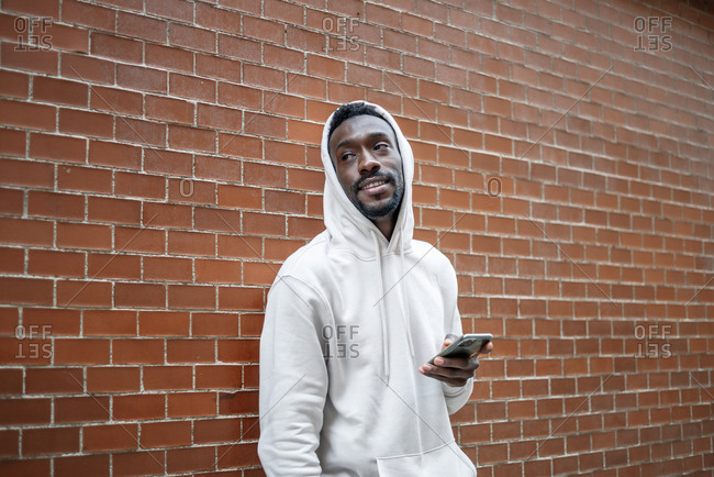 Side shot of African man with happy gesture and hood using smartphone in city