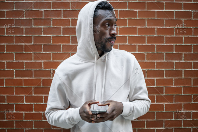 Front shot of African man with serious gesture and hood using smartphone in city
