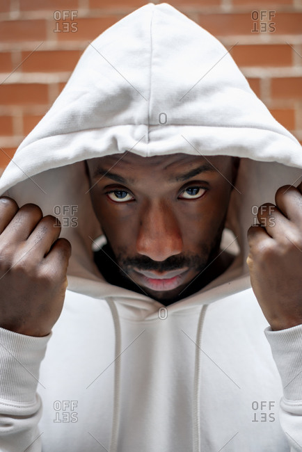 Front shot of African man with serious gesture covering his head with a white hood