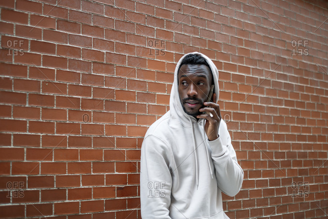 Side shot of African man with serious gesture and hood using smartphone in city