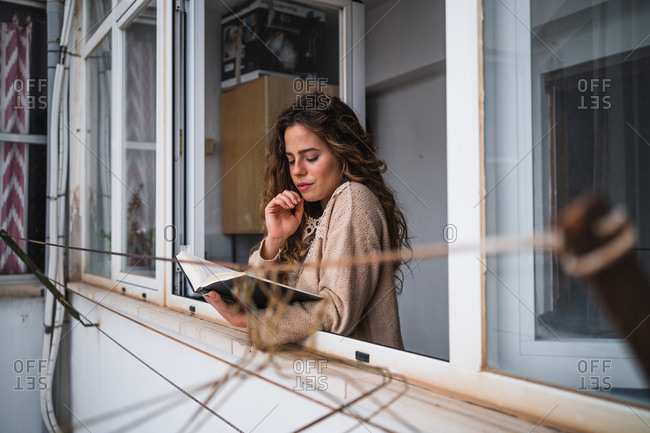 Young female reading book on a window