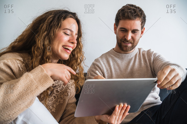 Delighted couple drawing on tablet together