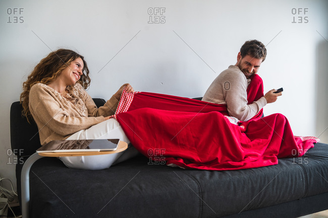 Happy couple fighting for blanket
