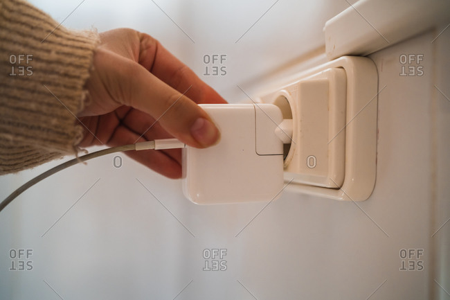 Crop person taking out plug of power socket