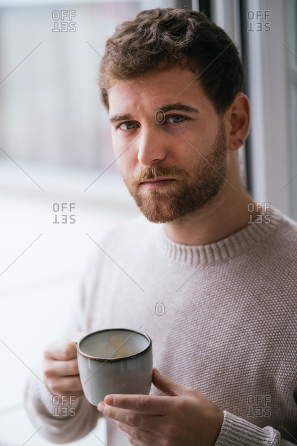 Serious male in sweater looking at camera while enjoying hot drink