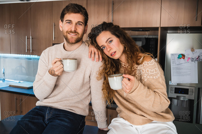 Young couple with hot beverage in kitchen at home looking at camera
