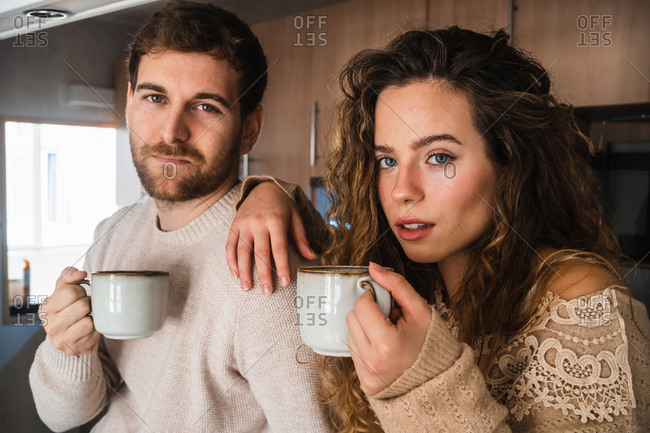 Young couple with hot beverage at kitchen at home looking at camera