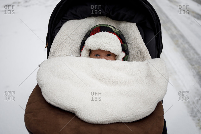 Newborn in warm hat lying in stroller during winter walk on snowy day