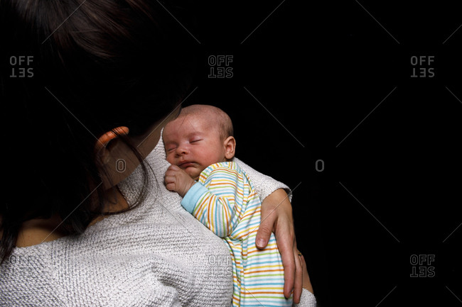 Cute baby sleeping peacefully in arms of unrecognizable loving mother