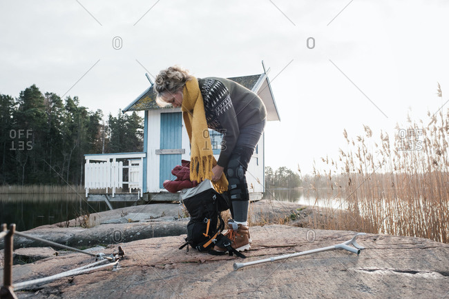 injured woman packing her bag at the beach ready to go camping