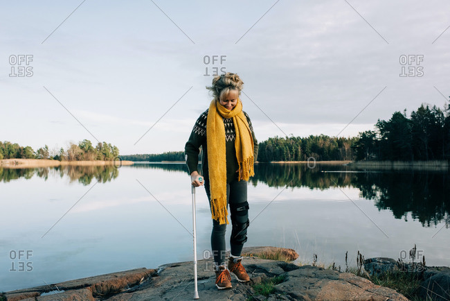 injured woman walking on the rocks with crutches in Sweden