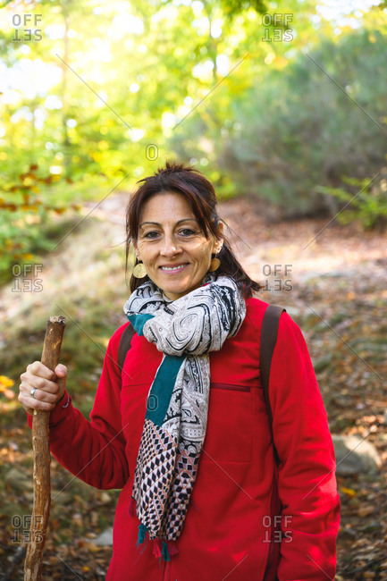 Smiling hiker woman holding a pole into forest while looking at camera