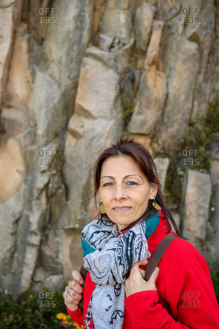 Laughing hiker woman with scarf and backpack, against stone formation