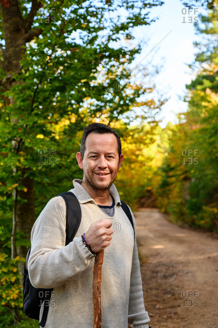 Smiling hiker man holding a pole into forest while looking at camera