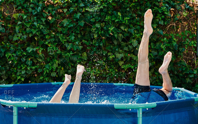Legs of two people jumping into a domestic swimming pool in garden.