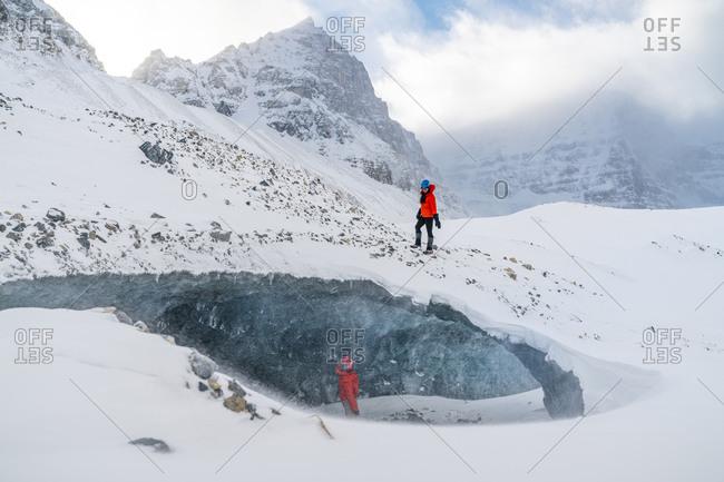 Couple Exploring Frozen Ice Cave In Glacier