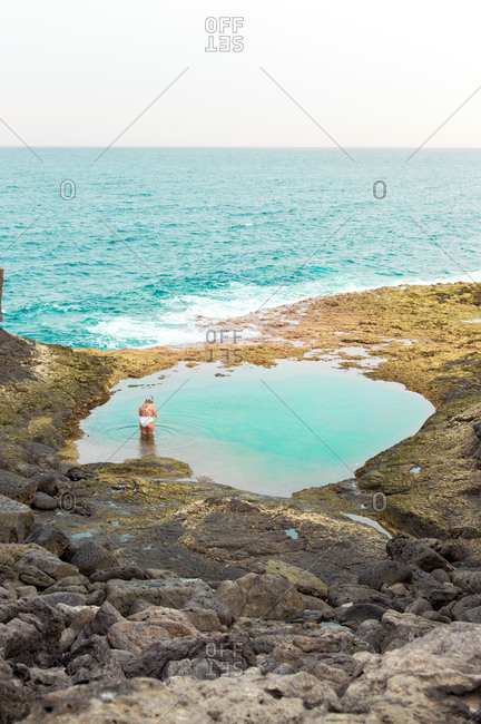 Young girl taking a bath in a natural sea pool in front of the sea.