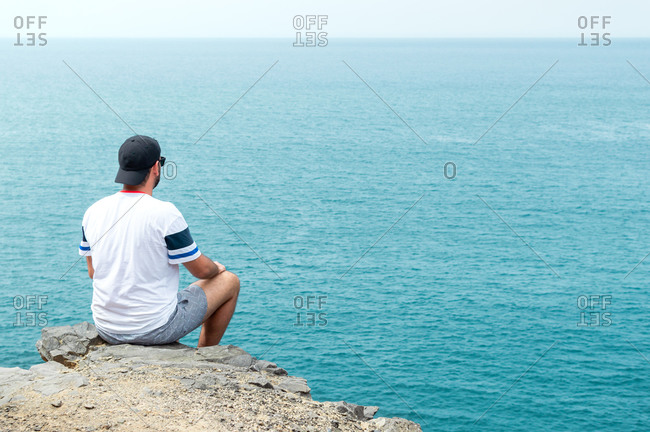 Young man with cap and sunglasses sitting on a cliff in front of the sea.