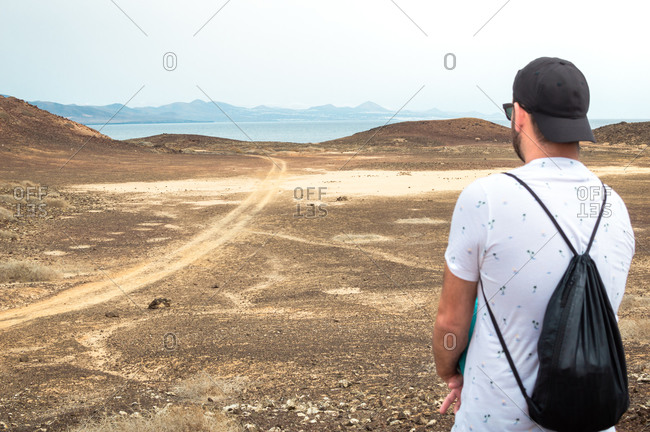 Traveler in a desert of Fuerteventura with the ocean in the background