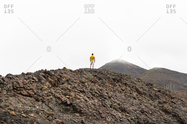 Back view of a man standing between clouds on top of a high mountain.