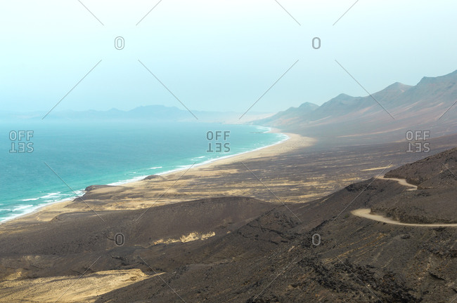 Landscape of Cofete beach and mountains in Fuerteventura, Canary Islands. Views of wild beach in Jandia natural park during a hazy day.
