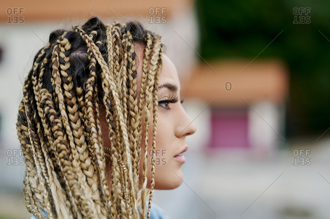 Close-up portrait of young woman with blonde colored braided hair looking to the side