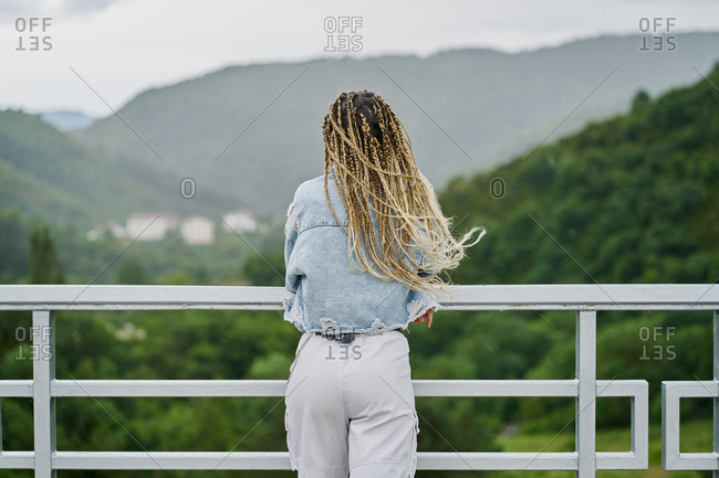 back side of a young woman with blonde braided hair wearing a denim jacket and white jean resting on a dam on a rainy day