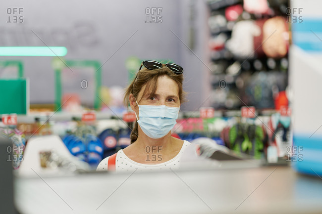 Woman wearing a medical mask choosing clothes in a shopping mall