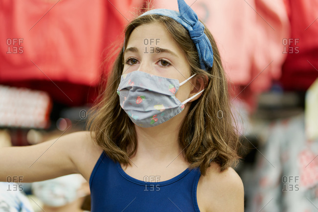 Girl with face mask shopping in clothes shop, coronavirus concept