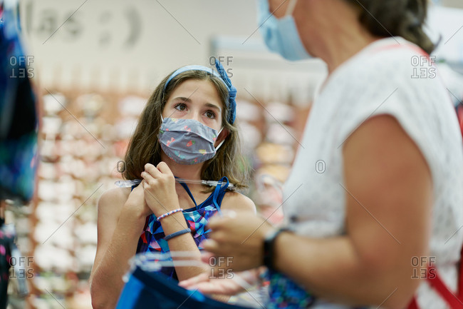 Mother and daughter wearing medical masks choosing a dress in a