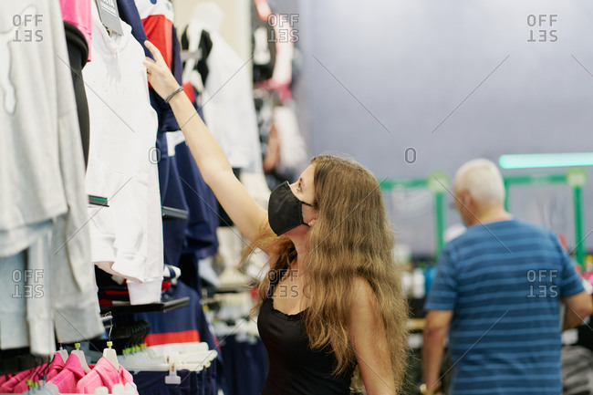 blond teenager with black face mask shopping in clothes shop, co