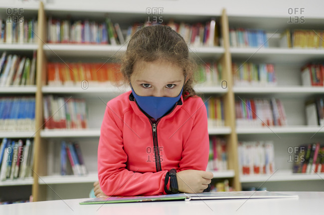 Little girl wearing a medical mask and reading a book in a library. Back to school concept