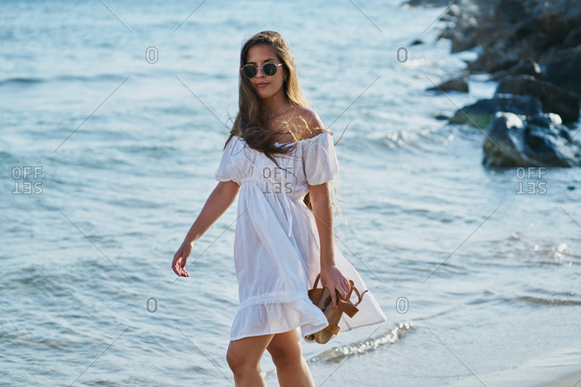 Young woman wearing sunglasses and wearing a white dress walking