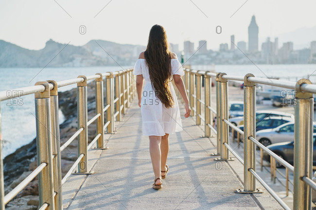 Back view of a young woman wearing a white dress walking on a pedestrian