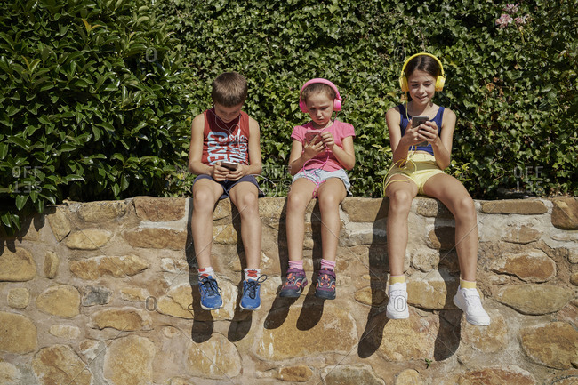 Boy and two girls looking at their smart phones and listening to music with headphones sitting on a stone wall in sunny day. Technology concept