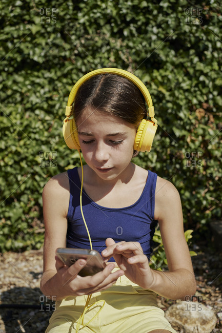 Beautiful girl listening to music with yellow headphones and holding a mobile device