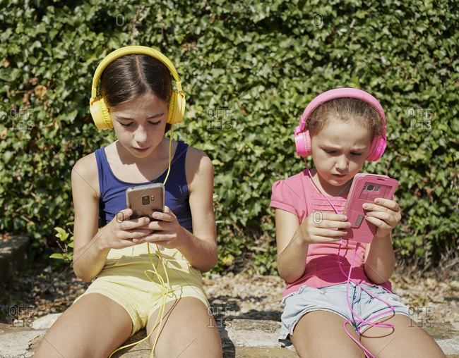 two girls looking at their smart phones and listening to music with headphones sitting on a stone wall in sunny day. Technology concept