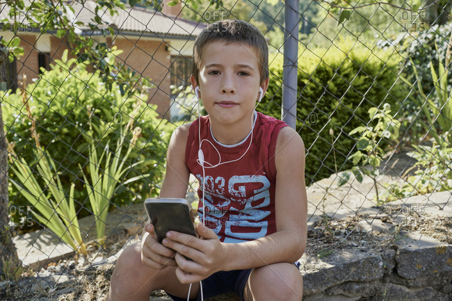 Boy looking at their smart phones and listening to music with headphones sitting on a stone wall in sunny day. Technology concept