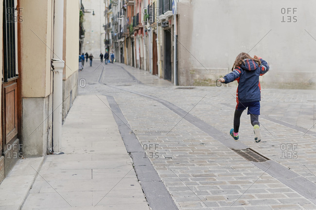 Girl jumping on a walk in the middle of a street in the old town