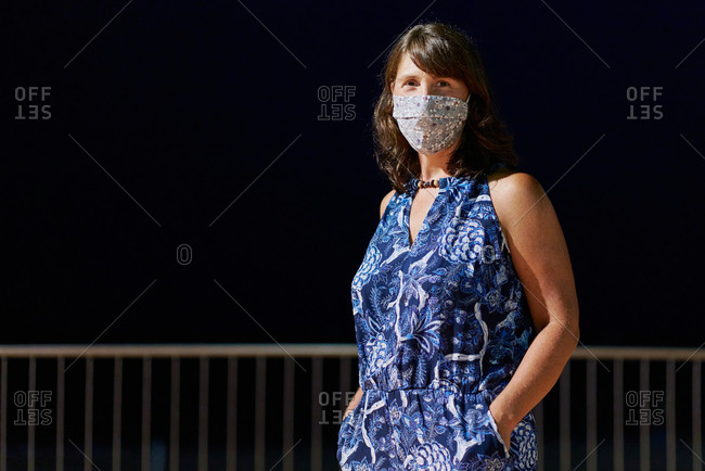 Portrait of a woman wearing a blue dress with flowers and a medical mask at night. Social event concept