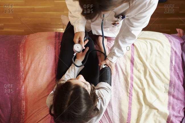 Top view of female doctor examining the pressure on a girl's arm in her bed. Home doctor concept