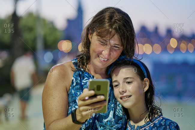Portrait of mother and teenage daughter wearing blue dresses and looking at the mobile at night with a beach in the background. Vacation concept