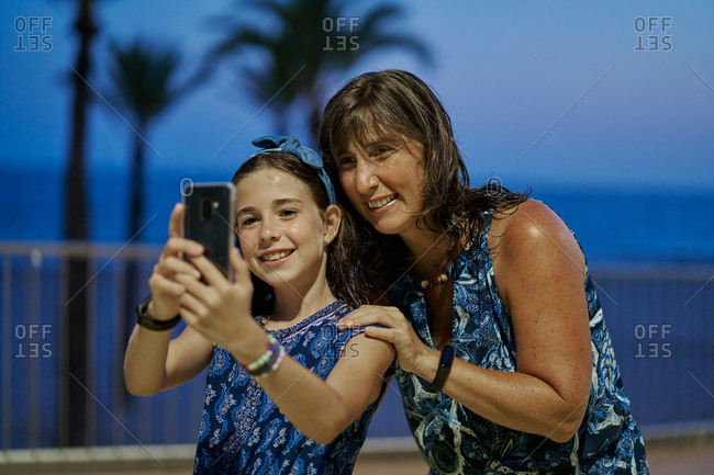 Portrait of mother and teenage daughter wearing blue dresses and taking a selfie with their smartphone at night with a beach in the background. Vacation concept