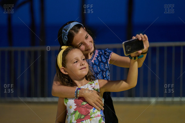 Portrait of two daughters wearing blue and white dresses and taking a selfie with their smartphone at night with a beach in the background. Vacation concept
