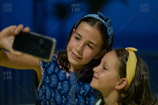Portrait of two daughters wearing blue dresses and taking a selfie with their smartphone at night with a beach in the background. Vacation concept