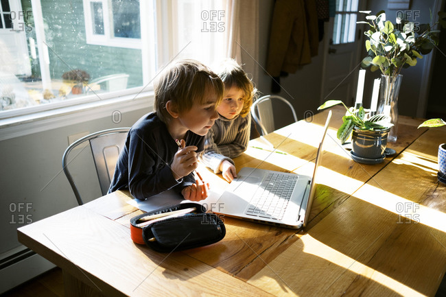 kids in morning light sitting at table doing remote school