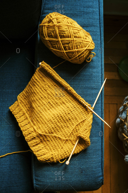 Detail of bright yellow knitting on a blue couch