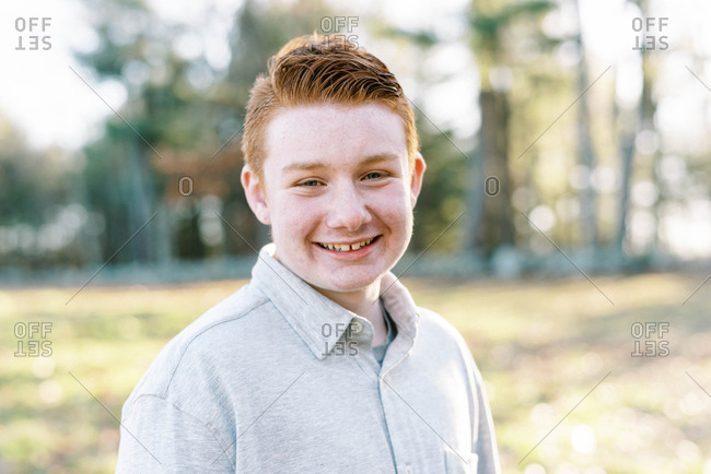 portrait of young ginger boy with blue eyes and freckles smiling