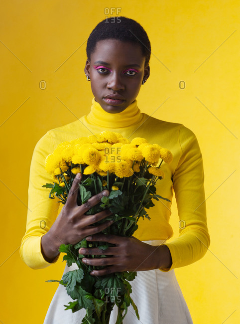 young fashionable black woman with bunch of yellow flowers isolated