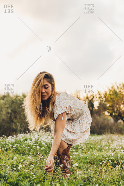 Woman In Nature Bent Over To Catch Some Flowers With Her Hands